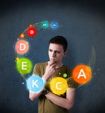 Young man thinking with vitamins circulation around his head Royalty Free Stock Photography