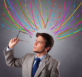 Young man thinking wiht colorful abstract lines overhead Royalty Free Stock Images
