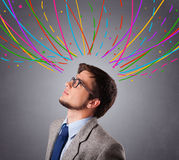 Young man thinking wiht colorful abstract lines overhead Stock Photo