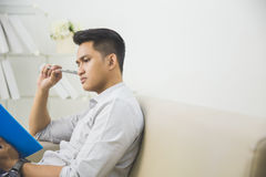Young man thinking while writing on a book Stock Images