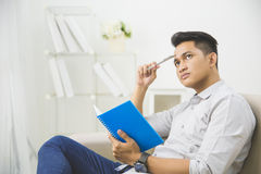 Young man thinking while writing on a book Stock Photography