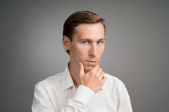Young man thinks, raising a hand to face. Young businessman in white shirt thinks, raising a hand to face Stock Photography
