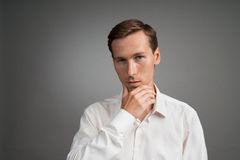 Young man thinks, raising a hand to face. Young businessman in white shirt thinks, raising a hand to face Royalty Free Stock Photo