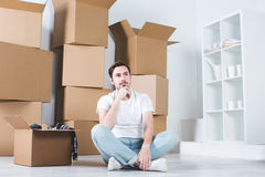 Young man thought sitting on the floor. Moving in house. Royalty Free Stock Photo