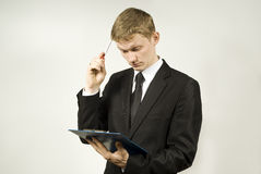 A young man thoughtfully looking at the plan. In the studio Stock Photography