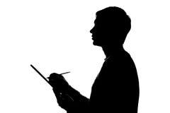 Young man thoughtfully writes, draws, writes. Silhouette Stock Photo