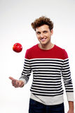 Young man throwing an apple up Stock Photography