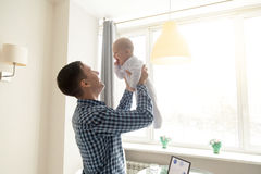Young man throwing a baby. Happy young father lifting cute baby up high in the air near the working place with laptop, spending and enjoying time together Stock Photo