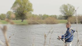 Young man throwing fishing rod in river on nature background stock footage