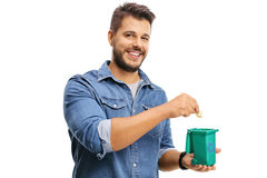 Young man throwing a piece of garbage in a recycling bin Royalty Free Stock Photo