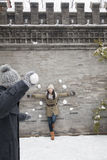 Young man throwing snow balls at young woman on wall Royalty Free Stock Photo
