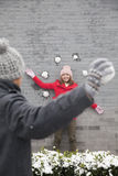 Young man throwing snow balls at young woman on wall Royalty Free Stock Images