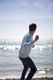 A young man throwing stones in the sea Royalty Free Stock Image