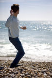 A young man throwing stones in the sea Royalty Free Stock Photos