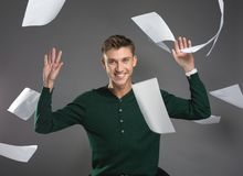 Young man throwing up papers with happy face stock images