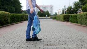 A young man throws out a package of garbage in the center of the city, litterbug stock footage