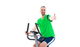 Man with thumb up train with fitness machine. Young man with thumb up train with fitness machine royalty free stock images