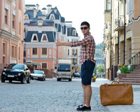 Young man thumbing a ride. Young man with a large suitcase thumbing a ride in an urban street with historic buildings as he hitchhikes his way around the country Stock Image