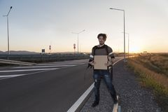 Young man thumbing on a road. Selective focus. Sunset time. Back light Royalty Free Stock Photos