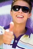 Young man with thumbs up. Smiling Royalty Free Stock Photos