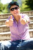 Young man with thumbs up. Smiling Royalty Free Stock Images