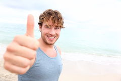 Young man thumbs up. Smiling happy sporty man giving thumbs up success sign to camera during training outside on beach. Handsome male fitness model in his 20s Stock Image