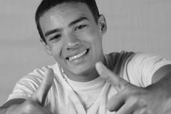 Young man with thumbs up. Black and white of young teen man giving the thumbs up sign with both hands Royalty Free Stock Image