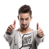 Young man with thumbs up. Casual portrait of a young man with thumbs up, over a gray background Royalty Free Stock Photo