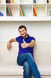 Young man with thumbs up. Handsome young man with thumbs up sitting on the sofa and smiling Royalty Free Stock Photography