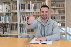 Young man with thumbs up happy and smiling with a book on the table in the library stock images