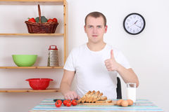 Young man thumbs up in the kitchen Royalty Free Stock Photography