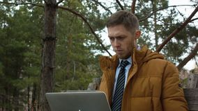 A young man in a tie uses a laptop on a bench in a forest park. A young man in a tie uses a laptop on a bench in a forest park stock footage