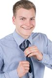 Young man ties up his necktie Stock Photos