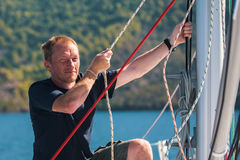 Young man tightens the ropes on the sails of the yacht. Royalty Free Stock Images