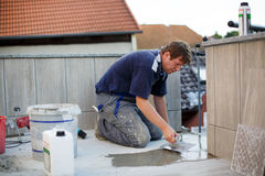 Young man tiling on balkony ceramic tiles Royalty Free Stock Image
