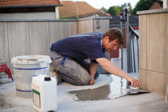 Young man tiling on balkony ceramic tiles Stock Images