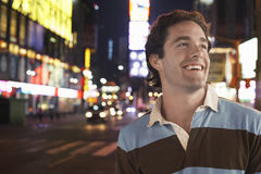 Young Man In Times Square New York At night. Closeup of a cheerful young man in Times Square New York at night royalty free stock photography