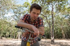 A young man is tired of riding a bicycle. It`s hot outside and he wants to drink. The concept of the inconvenience of traveling by bike Stock Images