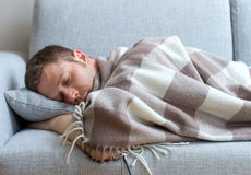 Young man tired. Young man tired and sleeping on the sofa stock image