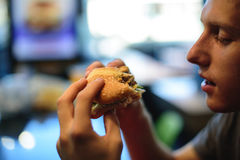 A young man is about to bite an appetizing burger. Stock Photos
