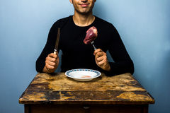 Young man about to eat a raw heart Royalty Free Stock Photos