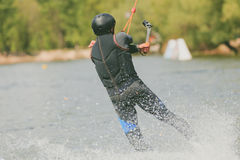 A young man to ride a Wakeboard, do tricks and shoot camera. Photo of grain processing Royalty Free Stock Images