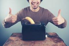 Young man toasting banana giving thumbs up Stock Photos