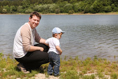 Young man with toddler boy on lake in summer Stock Photography