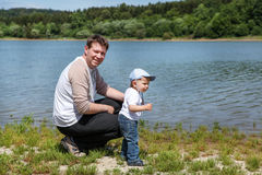 Young man with toddler boy on lake in summer Stock Photo
