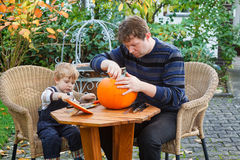Young man and toddler boy making halloween pumpkin Stock Photo