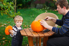 Young man and toddler boy making halloween pumpkin Royalty Free Stock Image