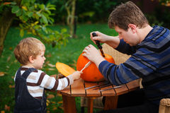 Young man and toddler boy making halloween pumpkin Royalty Free Stock Photography
