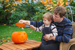Young man and toddler boy making halloween pumpkin Stock Image