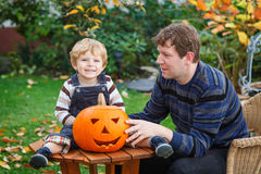 Young man and toddler boy making halloween pumpkin Stock Photos